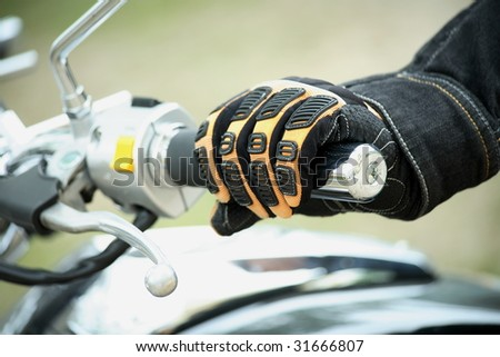 Biker hand rests on the steering wheel motorcycle - stock photo