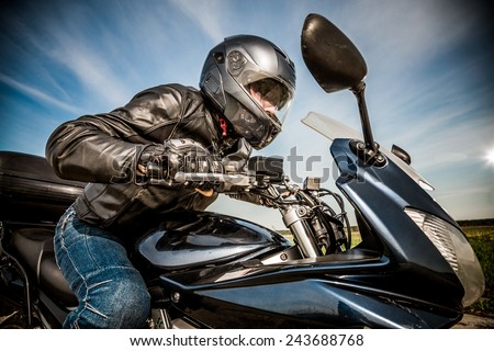 Biker in helmet and leather jacket racing on the road - stock photo