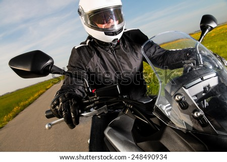 Biker in helmet and leather jacket riding on the road. - stock photo