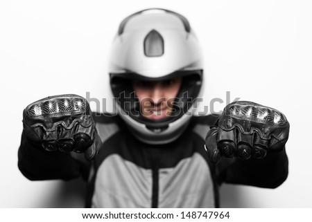 Biker in motorcycle jacket and helmet imitate driving. Studio shot. - stock photo