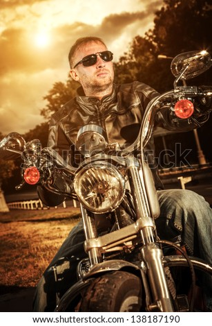 Biker in sunglasses and a leather jacket on a motorcycle - stock photo