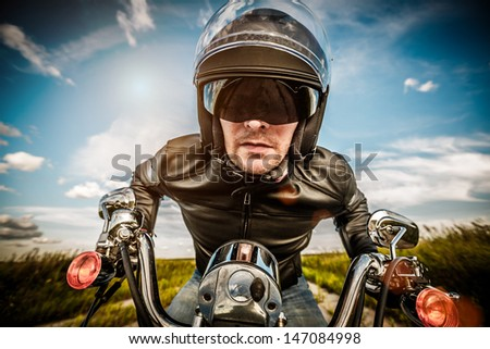 Biker in sunglasses and leather jacket racing on the road (fisheye lens) - stock photo