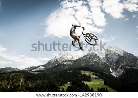 biker jumps a high stunt with mountains in the back - stock photo