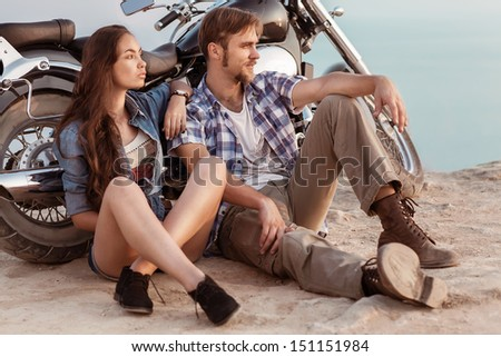 Biker man and girl sits  - stock photo