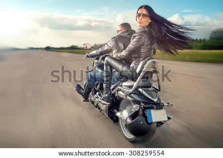 Biker Man and woman wearing black leather jackets and stylish sunglasses riding on motorcycle