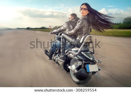 Biker Man and woman wearing black leather jackets and stylish sunglasses riding on motorcycle - stock photo