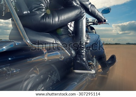 Biker Man and woman wearing black leather jackets riding on motorcycle - stock photo