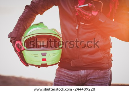 biker man helmet and mobile phone in hand sunset - stock photo