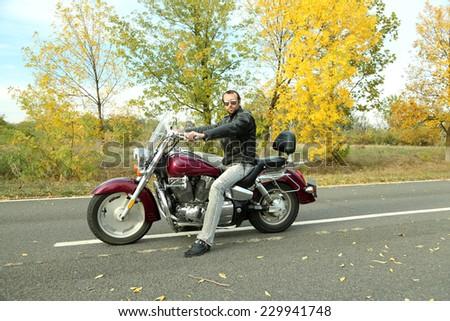 Biker man sits on bike - stock photo