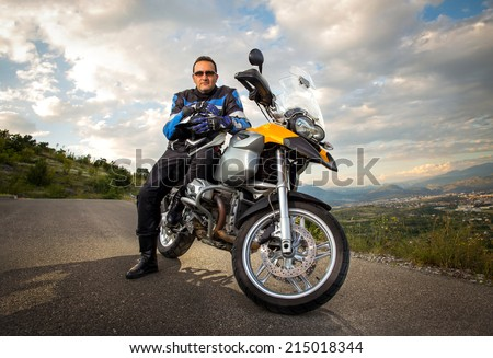Biker man sitting on his motorcycle - stock photo