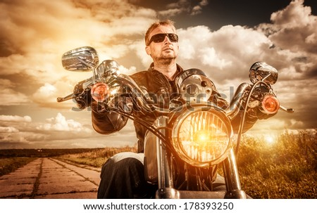 Biker man wearing a leather jacket and sunglasses sitting on his motorcycle looking at the sunset. Filter applied in post-production. - stock photo