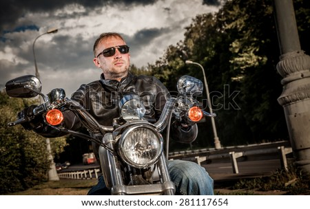 Biker man wearing a leather jacket and sunglasses sitting on his motorcycle looking at the sunset. - stock photo