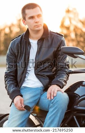 Biker man wearing a leather jacket and sunglasses sitting on his motorcycle outdoors - stock photo