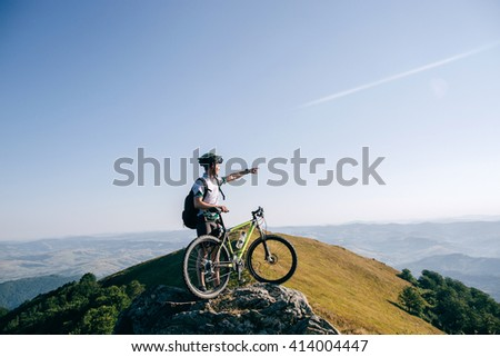 biker man  with the bike bicycle on top of the mountain looking into the distance, adventure, sport