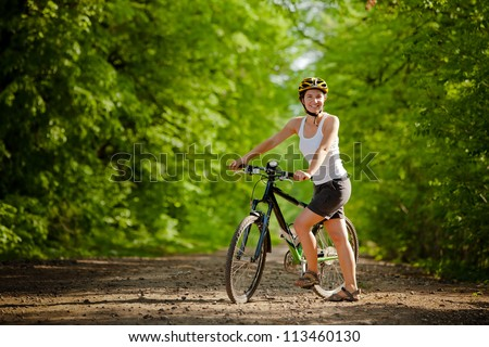Biker on the forest road - stock photo