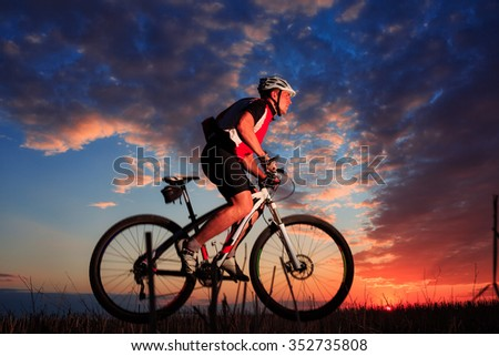 Biker on the meadow at the sunset against blue sky with clouds - stock photo