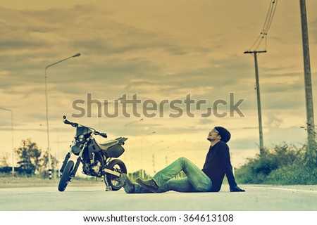 Biker relax sitting with motorbike on country road in sunset, cross process effect - stock photo