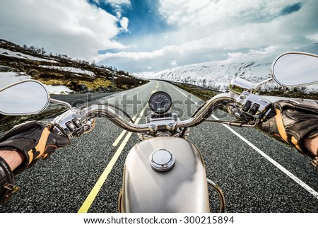 Biker rides a motorcycle on mountain serpentine. First-person view. - stock photo