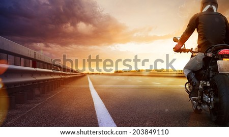 Biker riding motorcycle on an empty road at sunset - stock photo