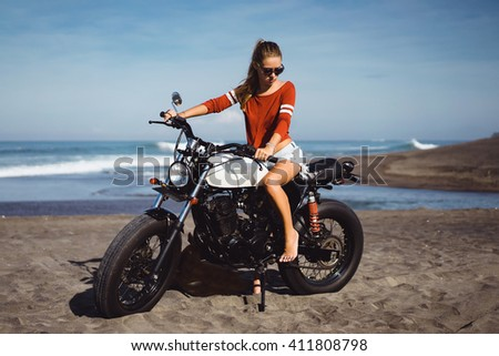 Biker sexy woman sitting on vintage custom motorcycle. Outdoor lifestyle toned portrait, posing near ocean, denim jeans style, hipster girl, caferacer, pretty hair girl on sunglasses and sport wear - stock photo