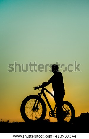 Biker silhouette of Retro bicycle in summer grass field at sun set