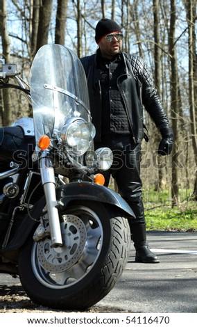 Biker stands near his bike , vertical - stock photo