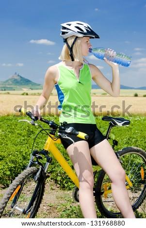 biker with bottle of water, Hazmburk, Ceske stredohori, Czech Republic - stock photo