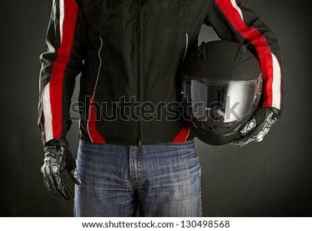 Biker with helmet in his hands. Dark background - stock photo