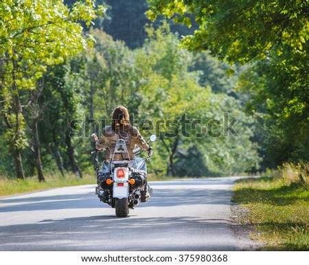 Biker with long hair riding motorcycle on road. View from the back - stock photo
