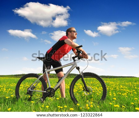 biker with the mountain bike in the dandelion field - stock photo