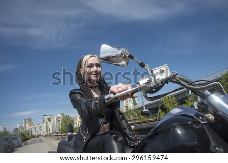 Biker Woman on motorcycle against blue sky with white clouds background Young brutal cute girl sit on chopper and wear black leather jacket and trousers  Empty space for inscription