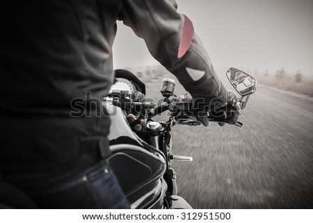 Bikers driving a motorcycle on misty asphalt road in black and white - stock photo