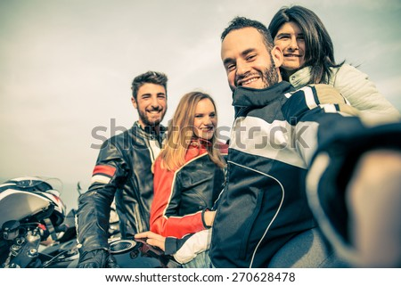 Bikers taking selfie with camera - Four smiling friends driving racing motorcycles with their girlfriends  - Two happy couples stop in a panoramic view point and photographing themselves - stock photo