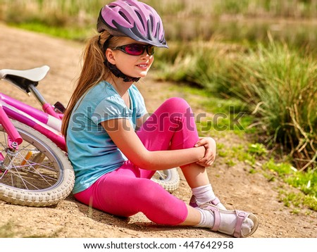 Bikes bicycle child . Happy child sitting on road near bicycles. Cycle racing concept. Child wearing bicycle helmet. - stock photo