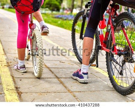 Bikes bicyclist girl. Children feet and bicycle wheel. Low section.  - stock photo