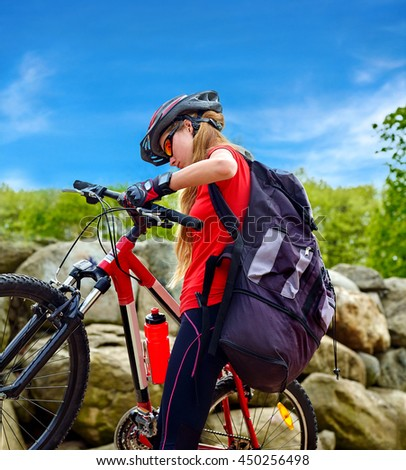 Bikes bicyclist girl. Girl rides bicycle into mountains. Girl on bicycle in mountaineering . Girl carries her bike over rocks. Bicyclist looks at his feet aganist blue sky. - stock photo
