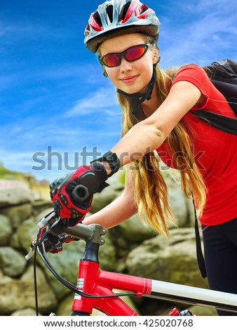 Bikes bicyclist girl. Girl wearing smart watch rides bicycle into mountains. Girl on bicycle in mountaineering  . Girl clings to wheel and looking at the camera. - stock photo