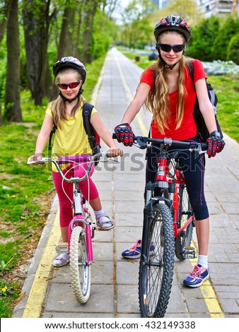Bikes bicyclist girl. Girls wearing bicycle helmet and glass with rucksack ciclyng bicycle. Girls children cycling on yellow bike lane. Bike share program save money and time at city street. - stock photo