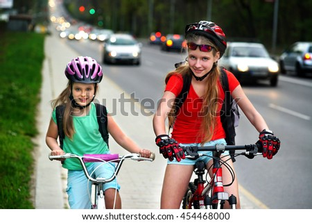 Bikes bicyclist girl. Girls wearing bicycle helmet and glasses with rucksack ciclyng bicycle. Girls children cycling on yellow bike lane at city street. There are cars on road.