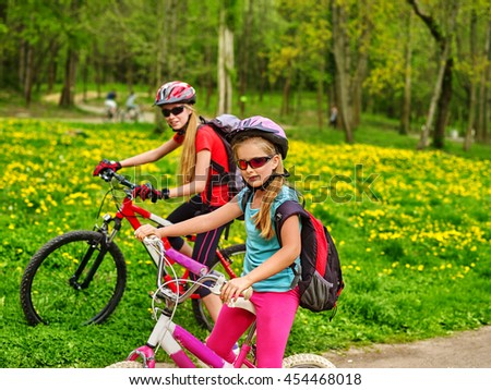 Bikes bicyclist girl. Girls wearing bicycle helmet and glasses with rucksack rides bicycle. Bicyclist children is looking at camera. Children ride on green grass and flowers in park. - stock photo