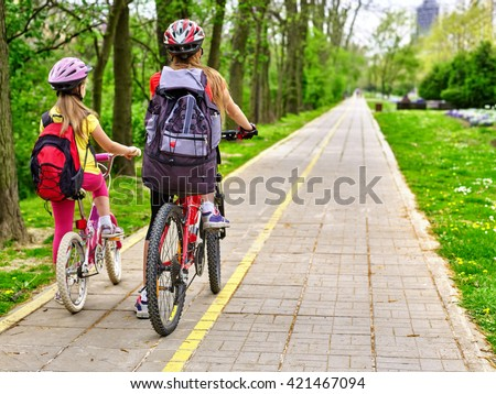 Bikes bicyclist girl. Girls wearing bicycle helmet  with rucksack ciclyng bicycle. Girls children cycling on yellow bike lane. Bike share program save money and time. Back view. - stock photo