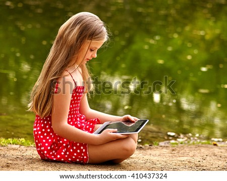 Bikes cycling girl into park.  Children watch tablet pc.  - stock photo