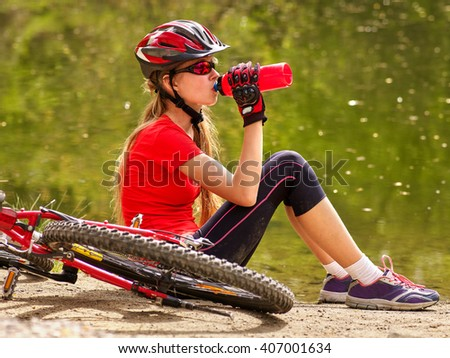 Bikes cycling girl wearing helmet. Girl cycling drinking of bottle water. - stock photo