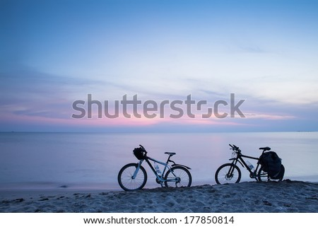 bikes parked in the sand dune along the beach on a bright sunny summer day at sunset. - stock photo