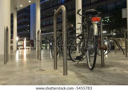 Bikes parked outside one of the ministries in the Hague, the Netherlands at night, one with a flat tire - stock photo