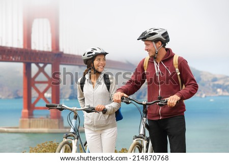 Biking Golden Gate Bridge - couple sightseeing in San Francisco, USA on bicycle. Young couple tourists on bike tour enjoying the view at the famous travel landmark in California, USA. - stock photo