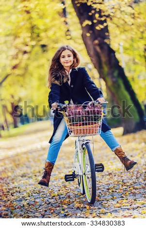 Biking, Young and beautiful girl on bike in autumn park