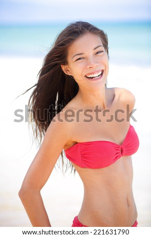 Bikini beach asian caucasian woman smiling happy on travel vacation holidays by blue ocean sea at tropical resort. Cheerful smiling excited mixed race girl laughing full of joy looking at camera. - stock photo
