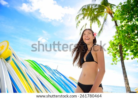 Bikini beach woman at surfboard rental surf shop. Happy Asian girl walking next to rack of many surf boards to rent for surf class on famous Waikiki beach, Honolulu City, Oahu, Hawaii, USA. - stock photo