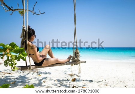 Bikini girl relaxing on tropical beach paradise in Thailand - stock photo
